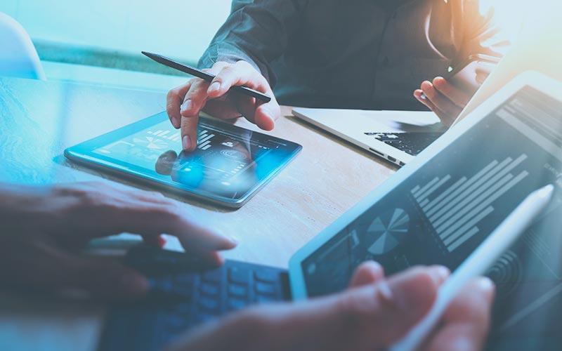 Pessoas com tablets e computadores fazendo a gestão financeira de suas empresas.